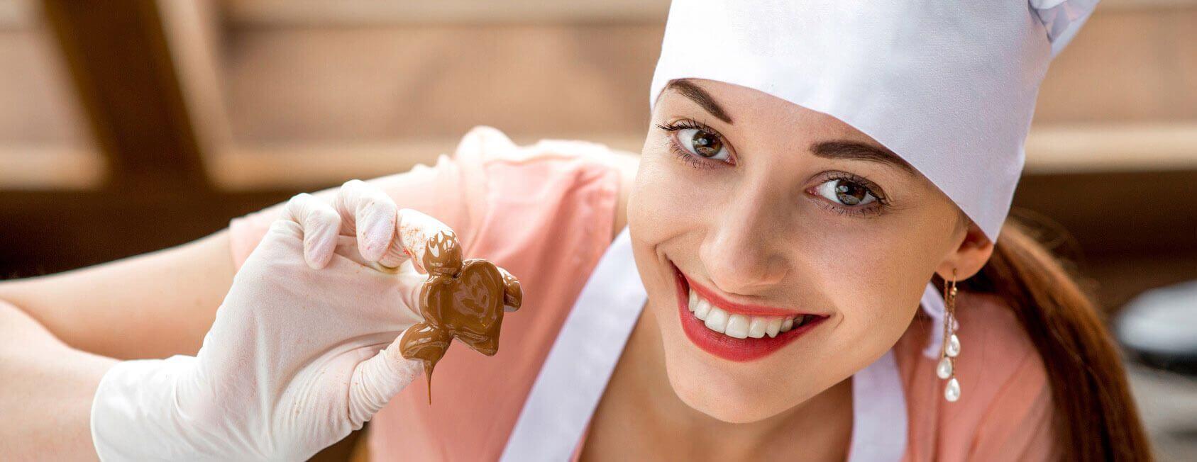 Frau mit einer selbstgemachten Praline in der Hand